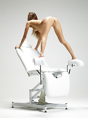 Cute blonde babe posing on ginecologic chair